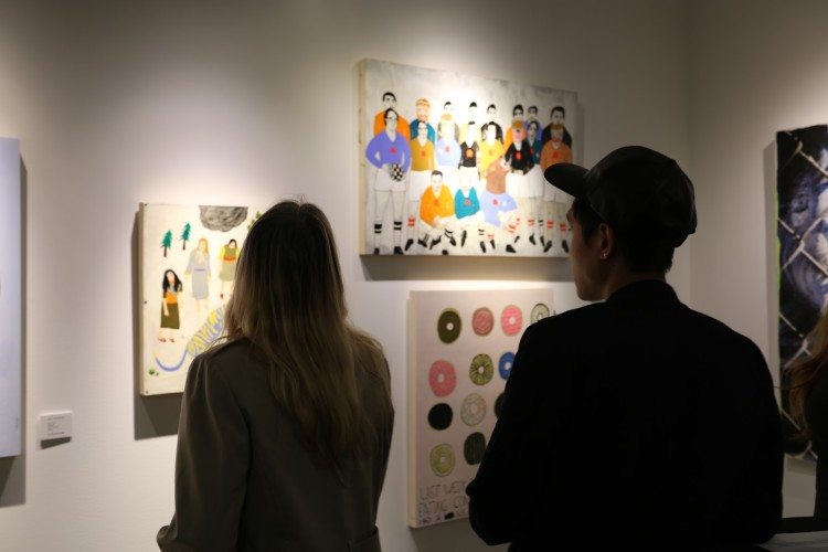 Visitors admire works by Kelly Puissegur