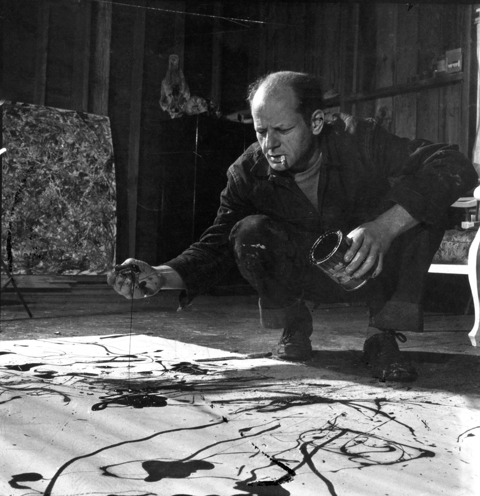 pollock drips paint onto the canvas, his signature style