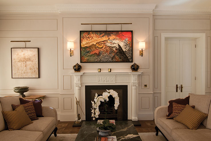 Textured modern abstract lit above a mantel in a traditional home