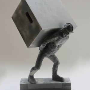 dark stone sculpture man holding large box figurative