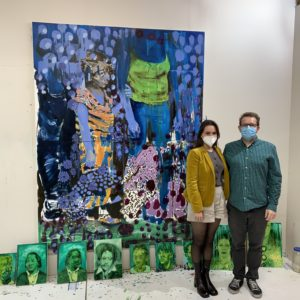 Fair Director Nicole Garton with artist Bartosz Beda in front of a blue painting, measuring 6 by 8 feet tall.