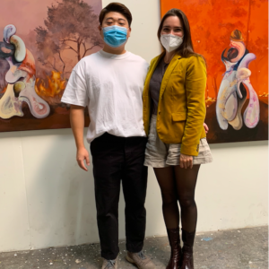 Fair Director Nicole Garton with artist Jay Chung in his studio, standing in front of 2 paintings